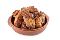 Barbecue chicken wings. Closeup of some barbecue chicken wings in an earthenware plate on a white background royalty free stock photography