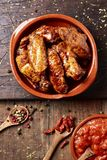Barbecue chicken wings. High angle view of some barbecue chicken wings in an earthenware plate and a bowl with barbecue sauce on a rustic wooden table royalty free stock photos