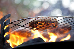 Barbecue cooking Burgers. Burgers on a Barbecue over flaming coals royalty free stock photography