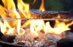 Barbecue cooking burgers. Burgers on a Barbecue over flaming coals royalty free stock images