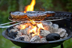 Barbecue Cooking Burgers. Burgers on a Barbecue over flaming coals royalty free stock photo