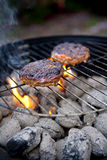 Barbecue cooking Burgers. Burgers on a Barbecue over flaming coals royalty free stock photos