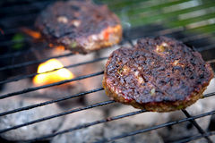 Barbecue Cooking Burgers. Burgers on a Barbecue over flaming coals stock images