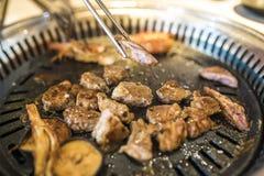 Barbecue coreano - la carne sta cucinanda sulla stufa immagini stock