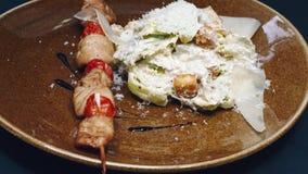 Barbecue de plan rapproché avec de la salade de la sauce et des biscuits avec du fromage dans un plat sur un fond noir dans la ré banque de vidéos