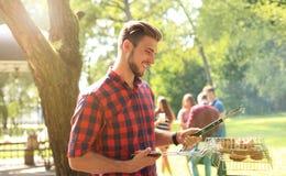 Barbecue de préparation masculin heureux beau dehors pour des amis Images stock
