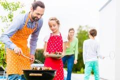 Barbecue della figlia e del padre insieme Immagine Stock Libera da Diritti