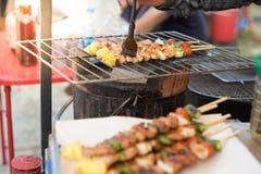 Barbecue della tenuta della mano ed arrosto di maiale fotografia stock