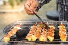 Barbecue della tenuta della mano ed arrosto di maiale fotografie stock