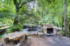 Barbecue di pietra e banchi e tavola di legno rustici accanto al mou Immagine Stock
