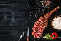 Barbecue dry aged rib of beef with spice, vegetables and a glass of light beer close-up on black wooden background Stock Photos