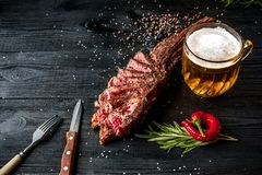 Barbecue dry aged rib of beef with spice, vegetables and a glass of light beer close-up on black wooden background Stock Photo