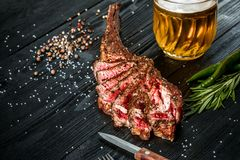 Barbecue dry aged rib of beef with spice, vegetables and a glass of light beer close-up on black wooden background Stock Images