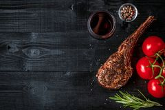 Barbecue dry aged rib of beef with spice, vegetables and glass of red wine close-up on black wooden background Royalty Free Stock Photo