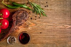 Barbecue dry aged rib of beef with vegetables and glass of red wine close-up on wooden background