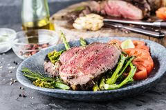 Barbecue dry aged wagyu tomahawk steak with green asparagus as top view on a wooden board. Barbecue dry aged wagyu tomahawk steak with green asparagus as top royalty free stock photos