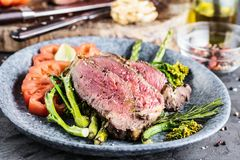 Barbecue dry aged wagyu tomahawk steak with green asparagus as top view on a wooden board. royalty free stock photos