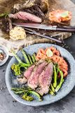 Barbecue dry aged wagyu tomahawk steak with green asparagus as top view on a wooden board. Barbecue dry aged wagyu tomahawk steak with green asparagus as top stock photography