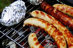 Barbecue en nature Saucisses et 'cuit au four de potatoesÑ photo stock