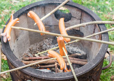 Barbecue with a fire pot and some Sausages on sticks Royalty Free Stock Photos