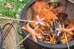 Barbecue with a fire pot and some Sausages on sticks.  Stock Image