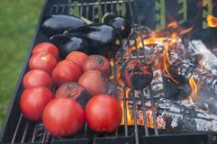 Making vegetables on grill- tomatoes and aubergines. Barbecue in the fresh air of delicious vegetables Royalty Free Stock Photos
