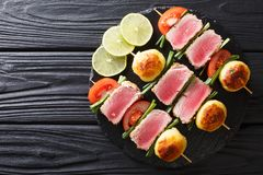 Barbecue of fresh tuna, tomatoes, potatoes and green onion on sk. Ewers close-up on the table. horizontal top view from above Royalty Free Stock Photography