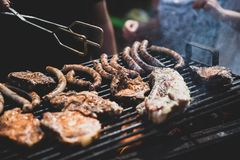 Barbecue, fry steaks, meat ribs and sausages. Weekend in nature, vacation with family and friends. Matte toning technique royalty free stock image