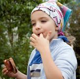 Barbecue girl. A cute girl eating a sandwich with sausage cooked on the barbecue, enjoying her meal Stock Photo