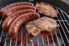 Barbecue Grill. Sausages an Meat on Barbecue Grill with Flames Stock Images
