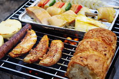 Barbecue Grill. Poultry, fish, bread and sausage on the barbecue grill Stock Photography