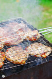 Barbecue grill. Steaks in Barbecue grill in smoke Stock Photos