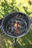 Barbecue Grill. In back yard or garden, seen from above, green grass, flames burning charcoal Stock Photography