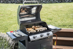 Barbecue grill bbq on propane gas grill steaks bratwurst sausages meat meal Royalty Free Stock Images