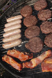 Barbecue grill with burgers and sausages. Barbecue grill with cooking burgers and sausages Stock Photography