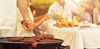 Barbecue grill with extended family having lunch in park Royalty Free Stock Photo