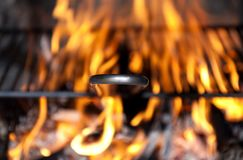 Barbecue grill on fire in fireplace. Black metal BBQ grill in live natural wood flame royalty free stock photos