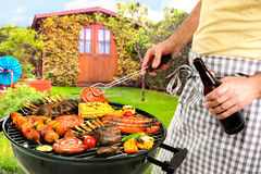 Barbecue grill. Man cooking meat on barbecue in front of backyard stock image