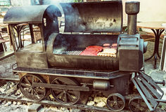 Barbecue grill with meat in shape of old steam locomotive, retro Stock Images