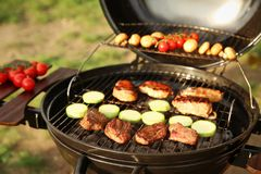 Barbecue grill with meat and vegetables outdoors, closeup. Camping cookout. Modern grill with meat and vegetables outdoors, closeup. Camping cookout royalty free stock photos