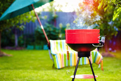 Barbecue grill with smoke on summer backyard party. Red barbecue grill with smoke on summer backyard party Stock Photos