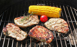 Barbecue grill. Steaks,corn on the cob and tomato on the barbecue grill Royalty Free Stock Photo