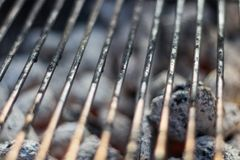 Barbecue grillage with hot coal briquets under it. Closeup of the center of the Barbecue royalty free stock images