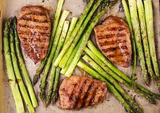 Barbecue grilled beef steak meat with asparagus and herbs. Top view royalty free stock image