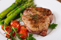 Barbecue grilled beef steak meat with asparagus. And tomatoes Royalty Free Stock Image