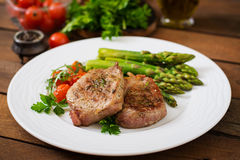 Barbecue grilled beef steak meat with asparagus. And tomatoes Royalty Free Stock Images