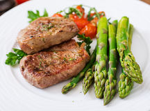Barbecue grilled beef steak meat with asparagus. And tomatoes Stock Photo