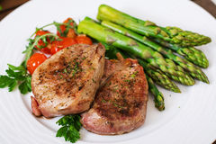 Barbecue grilled beef steak meat with asparagus. And tomatoes Royalty Free Stock Photo