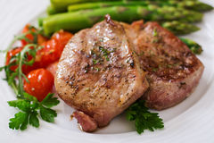 Barbecue grilled beef steak meat with asparagus. And tomatoes Royalty Free Stock Photography