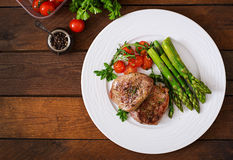 Barbecue grilled beef steak meat with asparagus. And tomatoes. Top view Royalty Free Stock Image